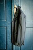 Mantel, der an einer Tür hängt Lizenzfreie Stockfotos