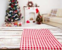 Mantel rojo a cuadros en la tabla de madera en el interior del día de fiesta, el Año Nuevo y el concepto borrosos de la Navidad,  foto de archivo libre de regalías