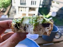 Mantendo a fatia do pão com pasta do abacate à disposição pronta para morder no café da manhã foto de stock royalty free