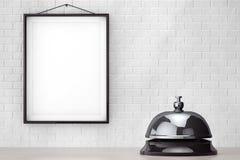 Mantenga el anillo de la campana delante de la pared de ladrillo con el capítulo en blanco Imágenes de archivo libres de regalías