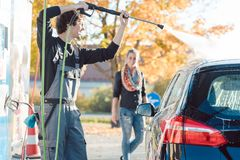 Mantenga a la mujer de ayuda del hombre que limpia su auto en túnel de lavado imagen de archivo libre de regalías