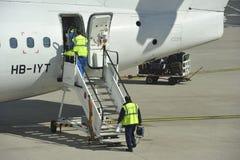 Mantenga a Team Entering el avión foto de archivo