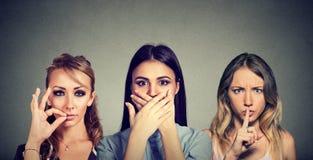 Mantenha um secreto para ser conceito quieto Três jovens mulheres secretos que mantêm a boca fechada imagens de stock royalty free