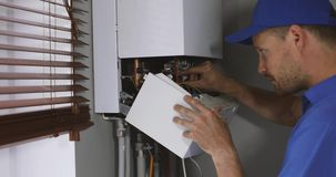 Mantenimiento y técnico de reparación que trabaja con la caldera de la calefacción de gas de la casa metrajes