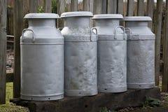 Mantequeras de leche en fila Imagen de archivo