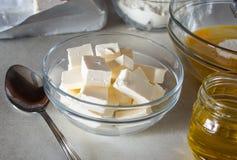 Mantequilla cortada en cuadritos en un cuenco en la tabla foto de archivo