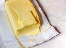 Mantequilla cremosa en su papel desempaquetado de la hoja E Fotografía de archivo