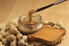 Mantequilla de cacahuete con los bizcochos tostados Fotos de archivo libres de regalías