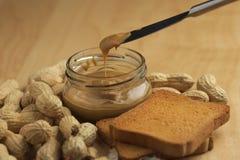 Mantequilla de cacahuete con los bizcochos tostados Imágenes de archivo libres de regalías