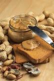 Mantequilla de cacahuete con los bizcochos tostados Imagenes de archivo