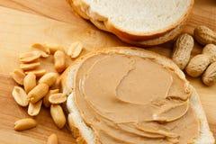 Mantequilla de cacahuete en el pan con los cacahuetes Fotos de archivo libres de regalías