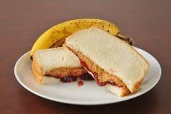 Mantequilla de cacahuete y bocadillo de la jalea con un plátano imagenes de archivo