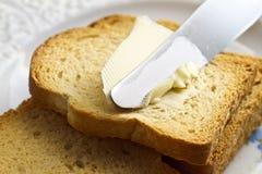 Mantequilla de extensión en el pan Fotografía de archivo