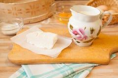 Mantequilla en el pergamino y la leche en jarro Imágenes de archivo libres de regalías