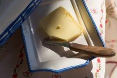 Mantequilla fresca en la placa con el cuchillo y el mantel de madera Imagenes de archivo