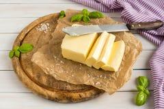 Mantequilla Rebanada de mantequilla Mantequilla cortada fresca en la placa de madera imágenes de archivo libres de regalías