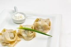 """Manti del †tradizionale kazako di cousine e dell'Uzbeco"""" su un piatto bianco Immagini Stock"""