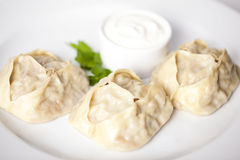 Manti dumplings ravioli great big huge with sour cream and parsley on a plate menu for the cafe restaurant  white backgrou Stock Photo