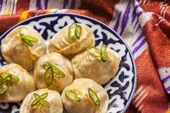 Manti nacional do alimento do Uzbeque em adras tradicionais da tela fotografia de stock