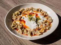 Manti turco con la pimienta roja, la salsa de tomate, el yogur y la menta Placa de la comida turca tradicional Visión superior fotos de archivo