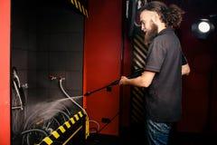 Mantiene el lavado profesional de una bicicleta en el taller Un hombre elegante caucásico joven con el pelo rizado largo hace un  imagenes de archivo