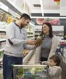 Mantimentos de compra da família no supermercado local foto de stock royalty free