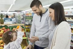 Mantimentos de compra da família de três membros nova no supermercado fotos de stock royalty free