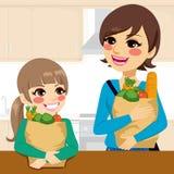 Mantimentos levando de ajuda da mãe da filha ilustração royalty free