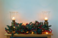 Mantle with green and red wreath and bronze candle holders. stock photos