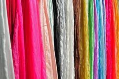 Mantones de seda coloridos que cuelgan en soporte de exhibición fotos de archivo libres de regalías