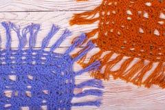 Mantones femeninos de lana hechos punto en fondo de madera Imagenes de archivo