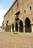 Mantovan arches & modern car. The ancient brick columns and cobbled plaza of Mantova, contrasting with a modern small car. Mantova, Italy stock images