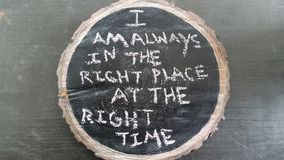 Mantra. I am always in the right place at the right time mantra written on black chalkboard with white chalk royalty free stock image