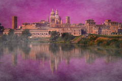 Mantua at the river reflecting in still waters at sunset. Ancient town of Mantua at the river reflecting in still waters at sunset with fog Stock Photos