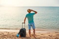 Manturist i sommarkläder med en resväska i hans hand som ser havet på stranden, begrepp av tid att resa arkivbild