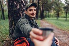 Manturist som ger koppen av varmt te till hans vän i begrepp för för vårskogför campa, resande och sport fotografering för bildbyråer