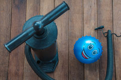 Manual air pump and elastic ball. Over the wooden floor Royalty Free Stock Image