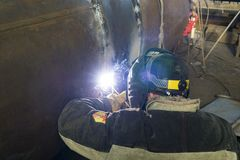 Manual arc welding. Welding of the shell of the heat exchanger. stock image