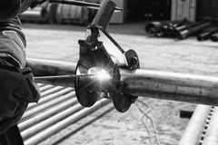 Manual arc welding of stainless steel pipe. The welder performs Assembly and joining of small diameter pipes with a special centralizer. Black and white photo Stock Photo