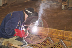 Manual arc welding. Welder fabricates piping elements. Manual arc welding Stock Image