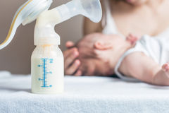 Manual breast pump with milk, mother and baby at background Royalty Free Stock Image