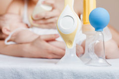 Manual breast pump and mother feeding a newborn baby Stock Photo