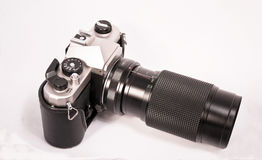 Manual camera with zoom lens. Shot of a isolated old manual camera with a zoom lens Royalty Free Stock Image