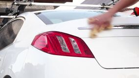 Manual car wash. A man washes his sedan from a special hose. Manual portable car wash. Detailed and gentle car care