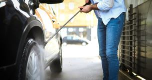 Manual car wash with pressurized water in car wash. Outside Stock Photos
