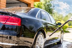 Manual car wash. Washing luxury vehicle with high pressure water pump.Automobile cleaning self service.  royalty free stock image