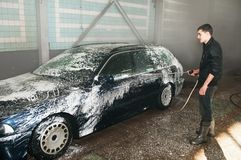 Manual car washing. Cleaning with foam and water at service station royalty free stock image