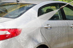 Manual car washing cleaning with foam and pressured water at ser Stock Photos