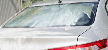 Manual car washing cleaning with foam and pressured water. At service station outdoor Royalty Free Stock Photo