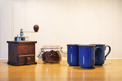 Manual coffee grinder and beans. Manual coffee grinder with beans and blue coffe cups on a bench Stock Images